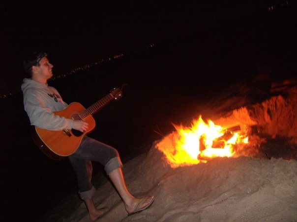 anthony playing guitar at night on the beach with campfire